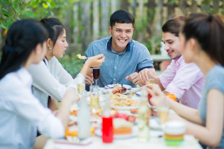 Grupo asiático comiendo la noche en que estaban hablando diversión Foto de archivo - 75527995