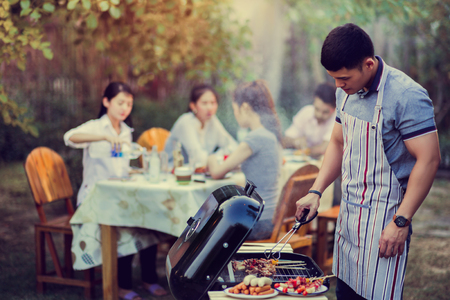 Asian men are cooking a barbecue for friends Imagens