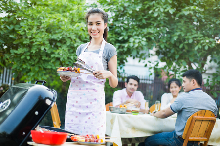 Asian women are cooking a barbecue to eat a friend Stock Photo
