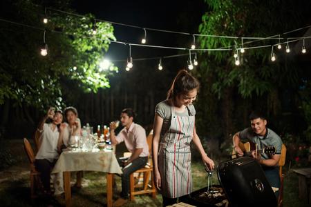 人アジア人バーベキュー パーティー前の庭