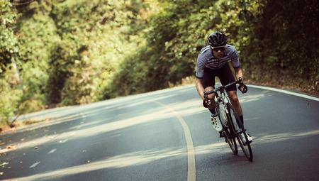 アジア人の男性が朝自転車道をサイクリングします。
