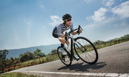 Les hommes asiatiques sont le cyclisme vélo de route le matin Banque d'images - 75499676