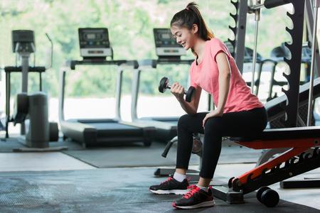 アジアの女性のトレーニングは、ジムでダンベルを持ち上げます。