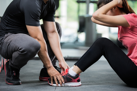 Trainer holding a woman in the leg exercise by Sid-ups. Banque d'images