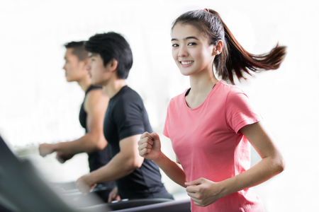 Asian women are exercising By running on a treadmill with her friends 版權商用圖片
