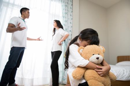 부모는 다투는 딸이 스트레스를 느끼고 있다고 느낍니다. 그녀는 울고, 곰 인형을 껴 안았다.