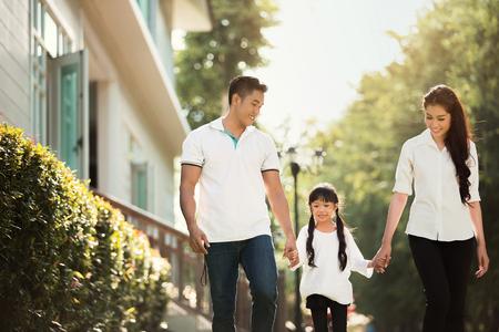 아시아계 가족이 집 밖으로 나갑니다. 부모와 자녀가 행복하게 함께 손을 잡고 걷고 있었다. 스톡 콘텐츠