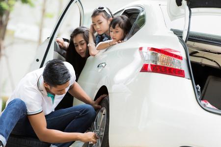 Padre fue a cambiar el neumático porque el neumático estaba goteando parque al lado de la madre y los niños animando