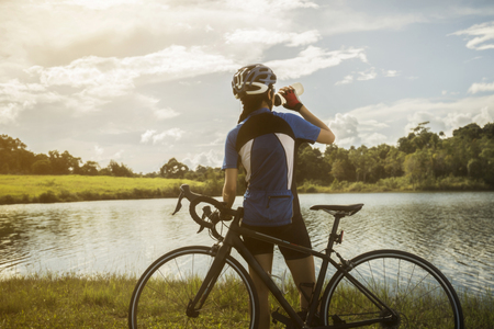 Woman cyclist relaxing drink water from the exercise Foto de archivo