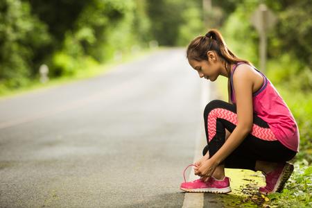 조깅하면서 여자가 묶인 신발 끈을 떨어 뜨 렸습니다. 스톡 콘텐츠