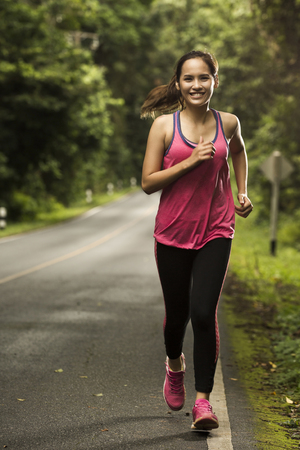 Asian woman were jogging on the road In the forest with sunny weather Stock fotó