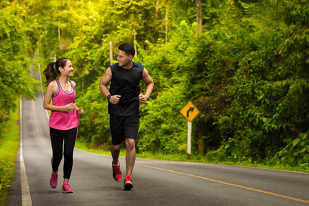 man and woman jogging in the forest