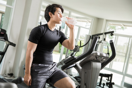 Asian men are drinking clean water While cycling exercise at the gym.
