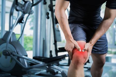 Gli uomini sani Infortuni dall'esercizio fisico in palestra, ha ferito il ginocchio Archivio Fotografico - 76412622