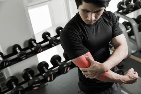 Men have been injured in the arm by a weight lifting exercise in gym 版權商用圖片 - 76302136