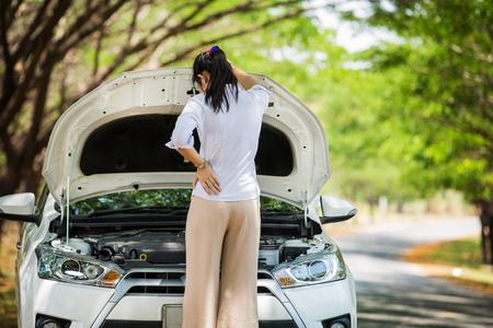 彼女は側にフードの壊れた車を開けた女性検査では、エンジンが破損しているかどうかを参照してください。