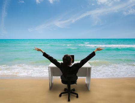 Werknemer is blij op het werk, zij werd herinnerd aan haar tijd om in de zomer op het strand te ontspannen Stockfoto