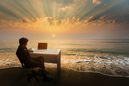 비즈니스 사람 (남자) 작업 준비가 해변에서 책상에 아침에 커피를 마시는. 스톡 콘텐츠