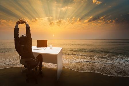 Werknemers werken tijdens rust en ontspanning Stel je voor dat je op kantoor zit. Op het strand in de ochtend. Stockfoto