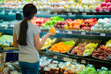 Woman are choosing fruit in supermarkets Imagens
