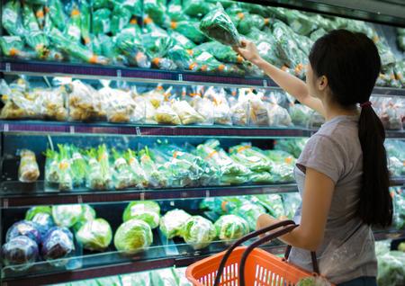 Woman are choosing vegetable in supermarket