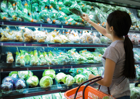 Woman are choosing vegetable in supermarket