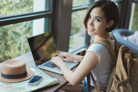 Woman asian travelers she shopping online or in flight. by internet at a coffee shop Stock Photo