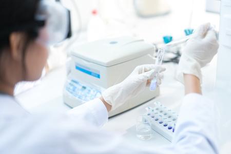 과학자들은 테스트 튜브에 물방울 화학 물질을 실험하고 있습니다. 스톡 콘텐츠