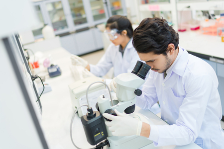 group of scientists working at the laboratory .she use microscope