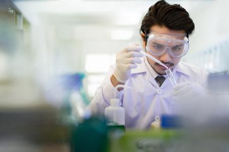 Aziatische wetenschapper in het laboratorium dat in laboratorium werkt met proefbuizen