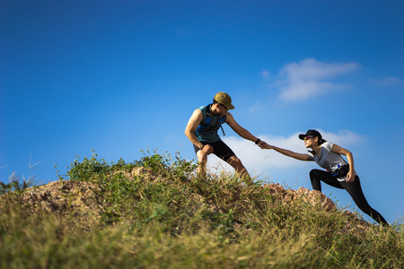 Trail runner are helping women runner from a slope. Stok Fotoğraf