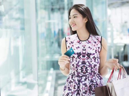 Mujer asiática con tarjeta de crédito para ir de compras en el centro comercial