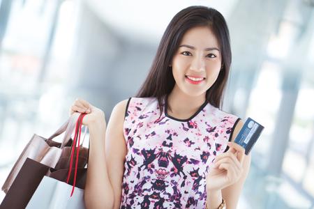 Aziatische vrouw die creditcard gebruiken om in de wandelgalerij te winkelen