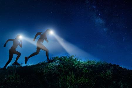 산에서 뛰고있는 남자와 여자의 나이트 트레일 러너. 밤의 유백색 길