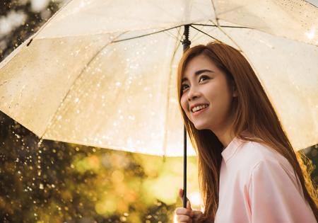 Asian woman waiting for the rain, she had an umbrella.
