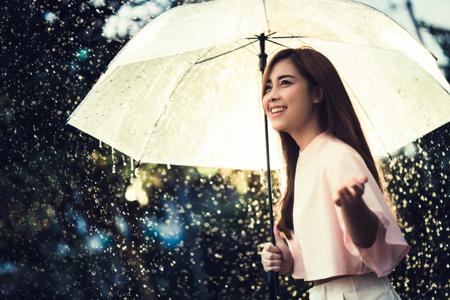アジアの女性が、雨を待っている彼女は傘を持っていた。 写真素材