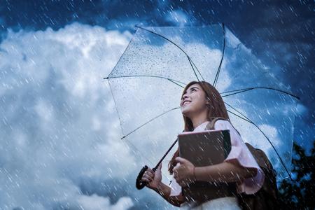アジアの学生が、雨を待っている彼女は傘を持っていた。 写真素材