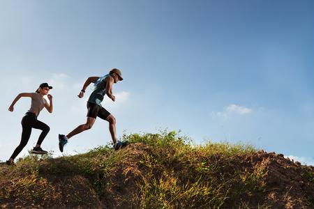 Trail Runner of men and women running on the mountain Imagens