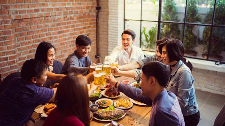 Persone in asian hanno celebrando il festival di tintinnano tazze di birra e cena felice Archivio Fotografico - 80828617