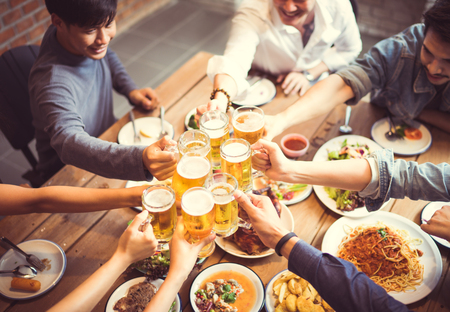 People in asian are celebrating the festival they clink glasses beer and dinner happy.top view Imagens