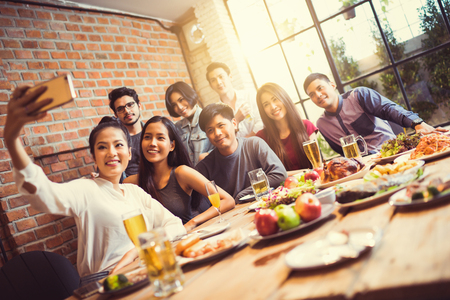 A group of friends are taking selfie friend told others He's coming to the party tonight.