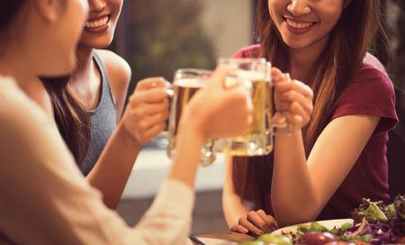 女性は、レストランでビールとチャリンという音メガネを飲んでいます。