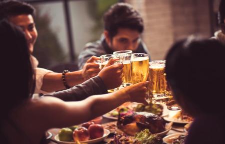 アジアの人々 は、彼らはガラス ビールと夕食幸せチャリンという音祭を祝っています。