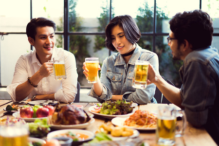 draughts: People in asian are celebrating the festival they clink glasses beer and dinner happy