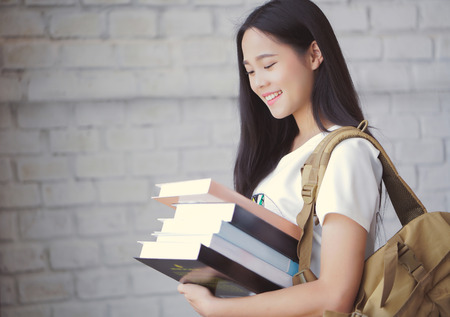 working on school project: Asian students holding books at university