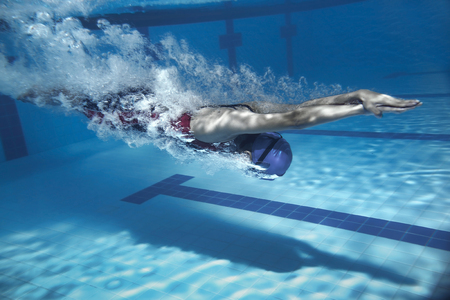 swimmer jump from platform jumping a swimming pool.Underwater photo