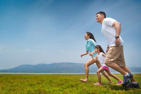 アジアの家族は開いた牧草地で実行されています。