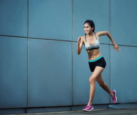 Asian woman a jogging at building a wall