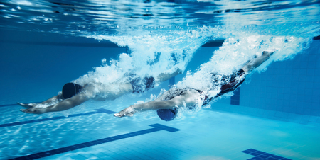 swimmer  Jump from platform jumping A swimming pool.Underwater photo Фото со стока