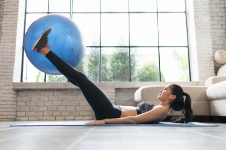 Asian women using an exercise ball in her house.